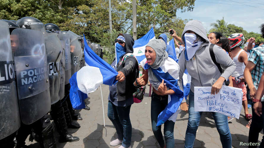 A demonstrator shouts slogans to riot police during a protest against Nicaraguan President Daniel Ortega's government in Managua, Sept. 23, 2018.
