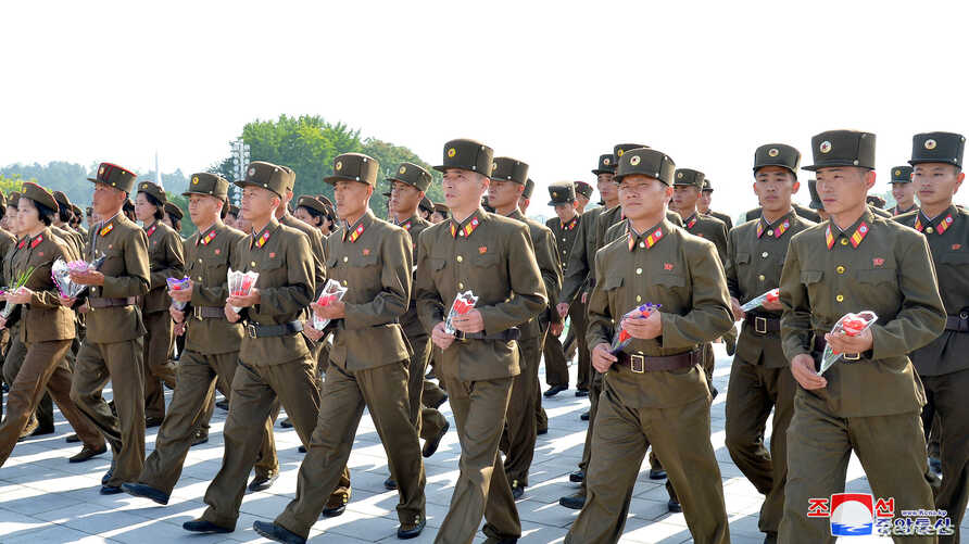 Soldiers gather to offer flowers to the statues of state founder Kim Il Sung and former leader Kim Jong Il on the Day of Songun at Mansu hill, Pyongyang, North Korea, in this undated photo released by North Korea's Korean Central News Agency, Aug. 26