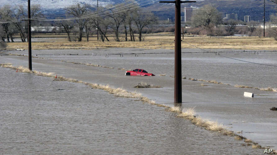 A red pickup truck sits abandoned it after it got stuck in floodwaters, Jan. 9, 2017, on a closed road at a University of Nevada, Reno, research farm bordering the Truckee River south of U.S. Interstate 80.