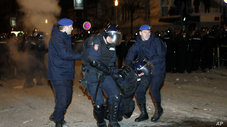FILE - In this Feb. 17, 2008, file photo, Serbian police officers carrying injured policeman in front of U.S. Embassy during a rally against Kosovo's declaration of independence, in Belgrade, Serbia.