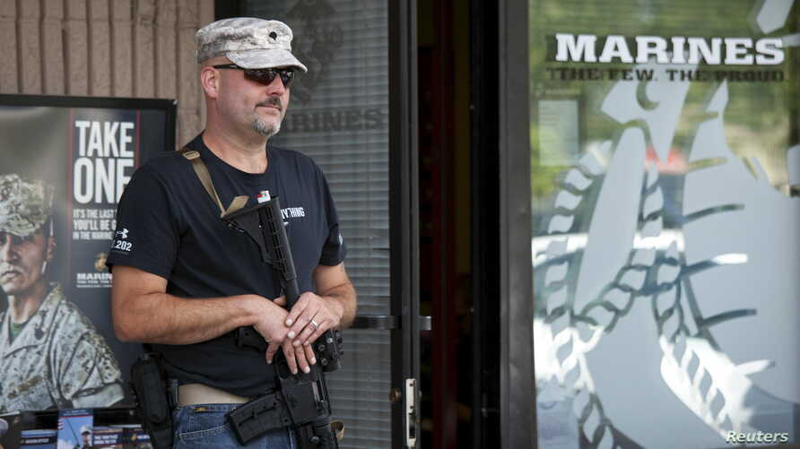 U.S. Army veteran Chris Murphy, armed with a rifle and handgun, stands near a U.S. Marines recruiting office in Everett, Washington July 23, 2015. According to the U.S. Army, citizens across the U.S. volunteered to station themselves near military re