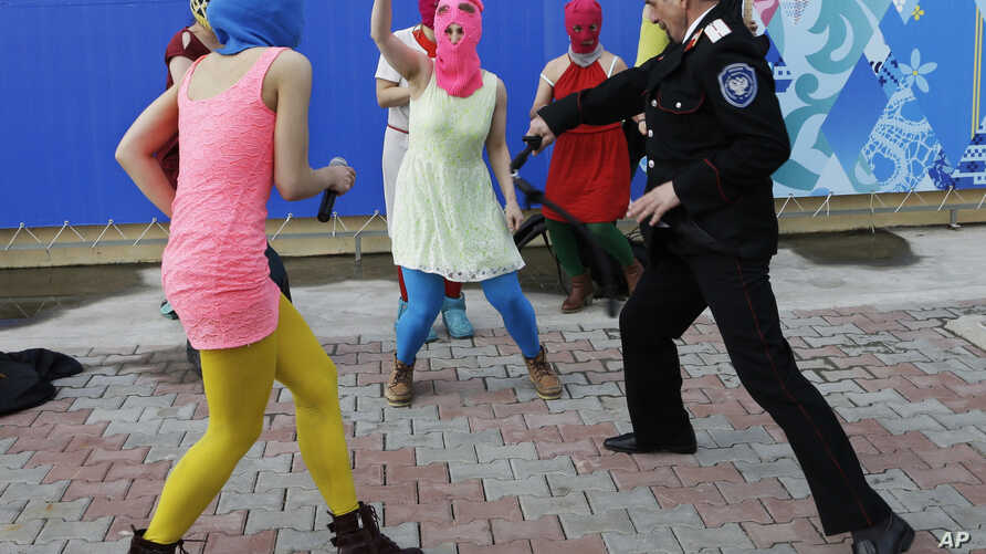 Members of the punk group Pussy Riot, including Nadezhda Tolokonnikova in the blue balaclava and Maria Alekhina in the pink balaclava, are attacked by Cossack militia in Sochi, Russia, on Wednesday, Feb. 19, 2014. The group had gathered in a downtown