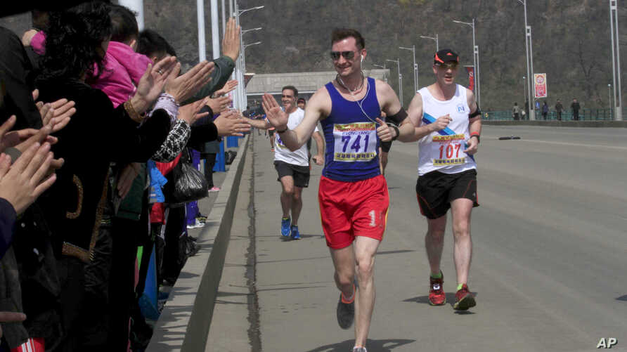 Runners are cheered by North Koreans during the Mangyongdae Prize International Marathon in Pyongyang, North Korea, April 10, 2016.