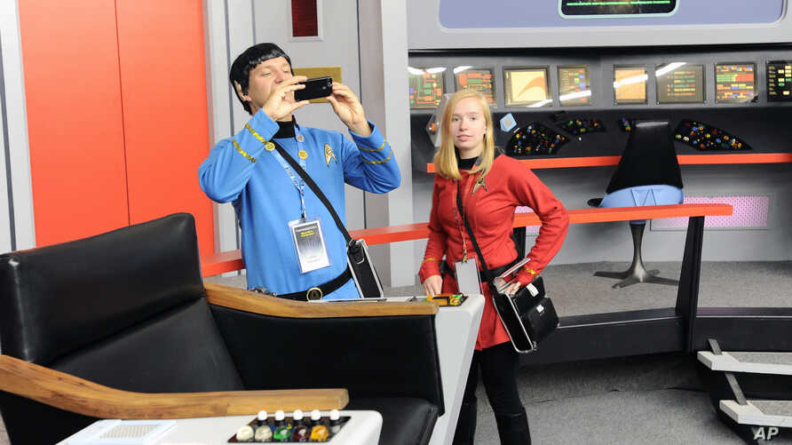 """Keith Schubert (L) of Peru, New York, dressed as Star Trek's Mr. Spock, and his daughter Tiffany, dressed as a crew member, take photographs during a tour of the replica starship Enterprise from the original """"Star Trek"""" series, in Ticonderoga, New Yo"""