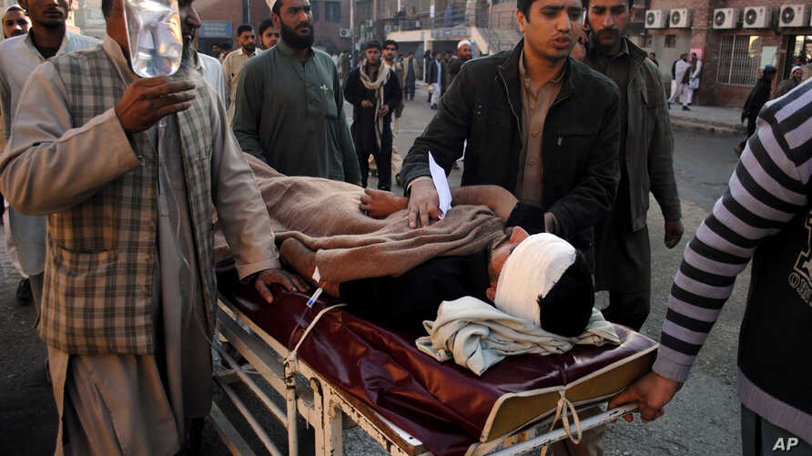 People care for a person injured in a blast on Dec. 3, 2012 in Peshawar, Pakistan.