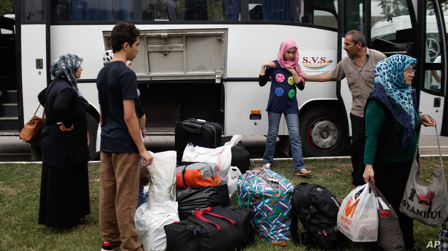 Syrian refugees prepare to board a bus for Istanbul, abandoning plans to cross to Europe near Turkey's western border with Greece and Bulgaria, in Edirne, Turkey, Wednesday, Sept. 23, 2015.