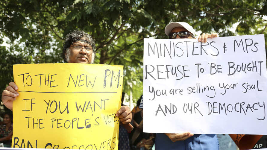 Sri Lankan civil rights activists hold placards during a demonstration outside the official residence of ousted Prime Minister Ranil Wickremesinghe in Colombo, Sri Lanka, Nov 4, 2018.