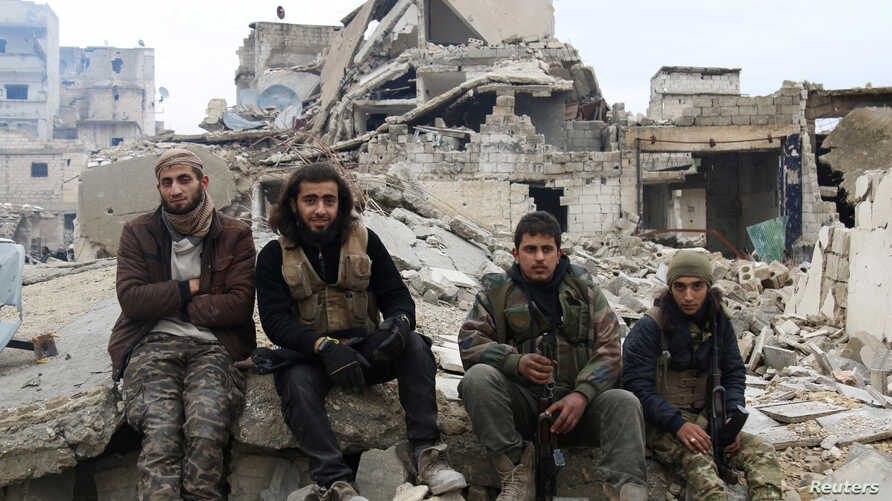 Rebel fighters sit on the rubble of damaged buildings as they wait to be evacuated from a rebel-held sector of eastern Aleppo, Syria Dec. 16, 2016.