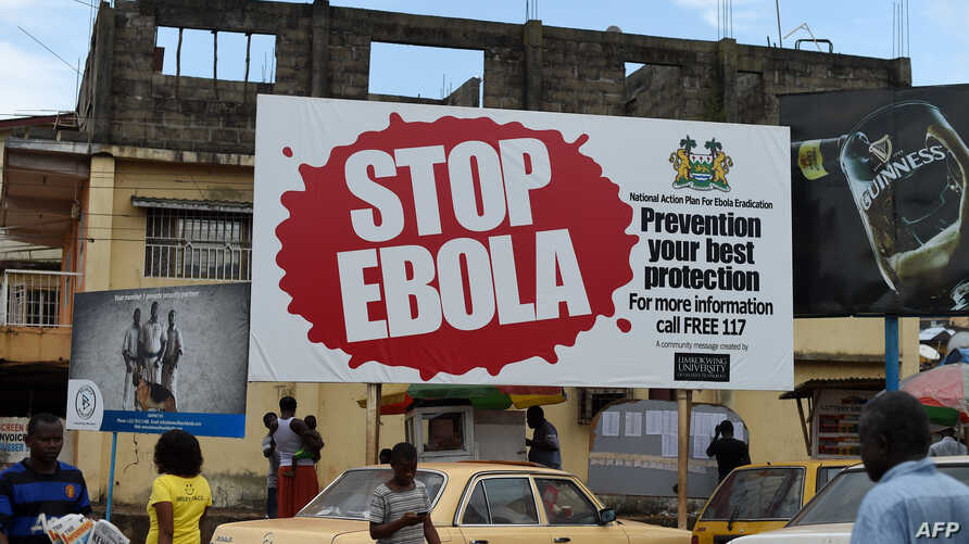 "FILES - People walking past a billboard reading ""Stop Ebola"" in Freetown, Sierra Leone, Nov. 7, 2014."