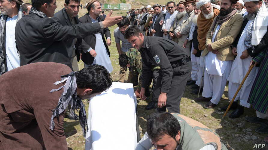 Afghan mourners handle the coffin for a victim killed in the April 19 Taliban truck bomb attack, in Kabul on April 20, 2016.