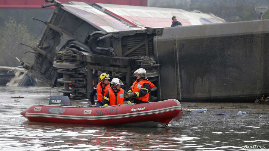 Rescue workers on a small boat search the wreckage of a test TGV train that derailed and crashed in a canal outside Eckwersheim near Strasbourg, eastern France, Nov. 14, 2015.