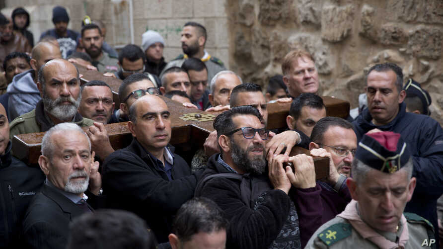 Christian worshippers hold a cross as they walk along the Via Dolorosa towards the Church of the Holy Sepulchre, traditionally believed by many to be the site of the crucifixion of Jesus Christ, during the Good Friday procession in Jerusalem's Old Ci