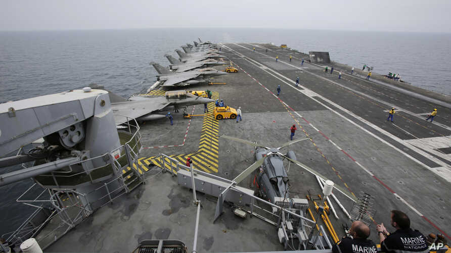 FILE - French sailors work on the flight deck of the French Navy aircraft carrier Charles de Gaulle in the Persian Gulf, March 17, 2015.