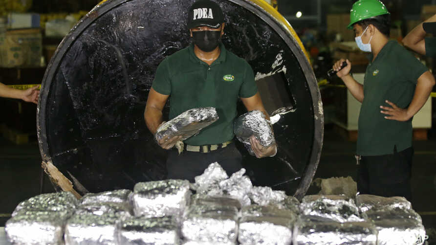 """A member of the Philippine Drug Enforcement Agency, PDEA, collects packs of Methamphetamine Hydrochloride also known as """"Shabu"""" which they found hidden inside a steel cylinder in one of the biggest drug hauls in Manila, Philippines, on Aug. 7, 2018."""