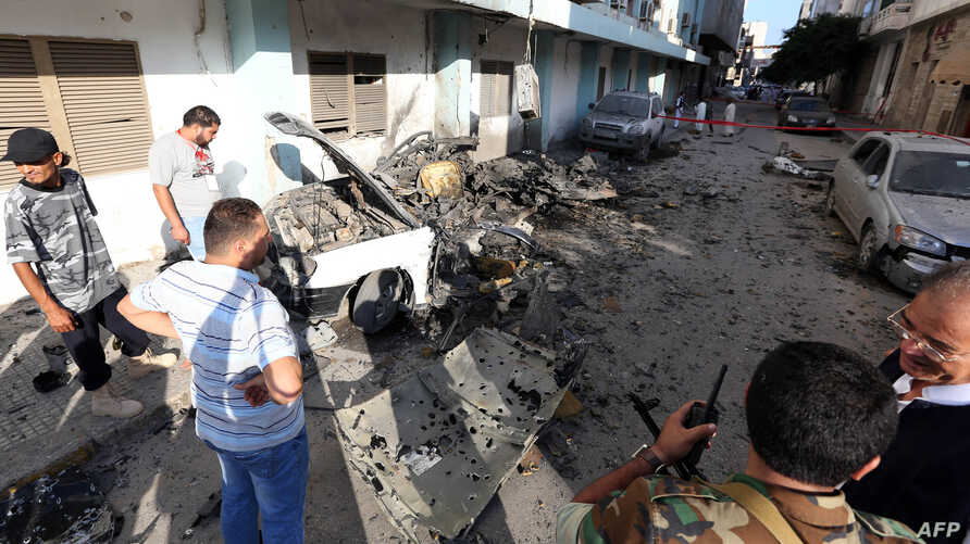 Libyan security forces inspect the remains of a vehicle near the Ministry of Interior in Tripoli after twin blasts hit the Libyan capital, August 19, 2012.