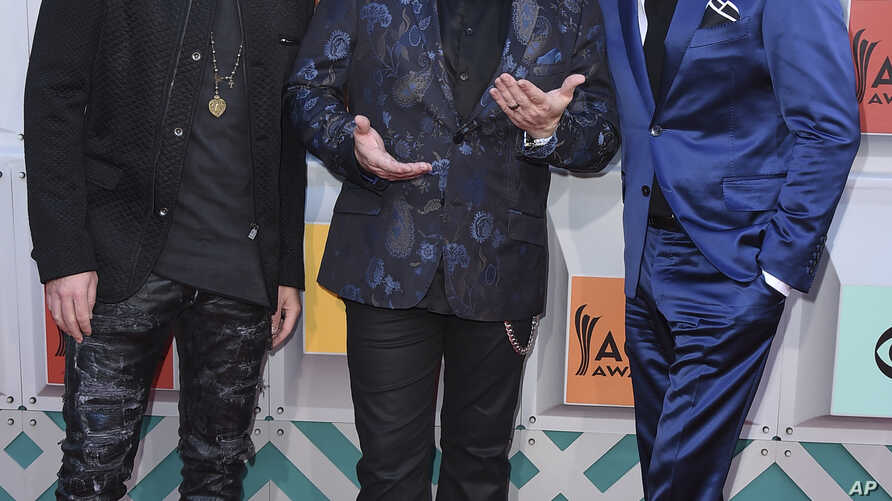 FILE - Joe Don Rooney, from left, Gary LeVox, and Jay DeMarcus, of Rascal Flatts, arrive at the 51st annual Academy of Country Music Awards in Las Vegas, April 3, 2016.