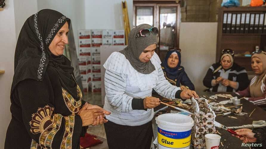 Syrian refugee Sameera Al Salam shows a colleague how to strengthen a paper handbag with glue, at an up-cycling workshop in Irbid city, northern Jordan, May 9, 2018.