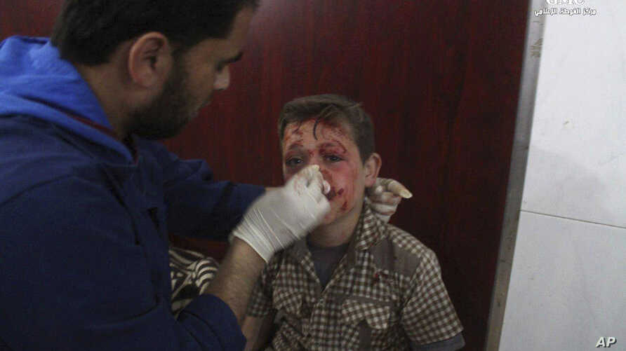 This photo provided by the Syrian anti-government activist group Ghouta Media Center, which has been authenticated based on its contents and other AP reporting, shows a Syrian doctor treating a boy who was wounded by Syrian government forces shelling