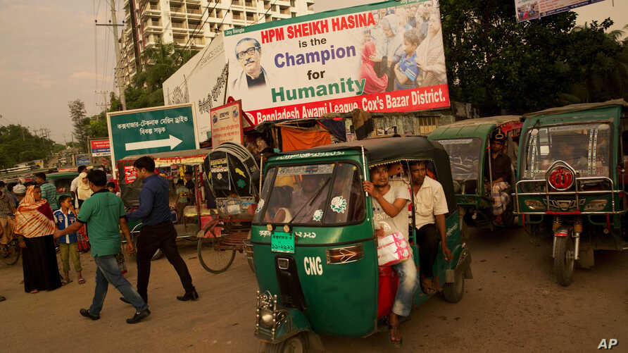 FILE - Bangladeshis crowd a tuk-tuk on a street with a billboard in appreciation of Bangladesh's Prime Minister Sheikh Hasina for sheltering Rohingya Muslims fleeing Myanmar, in Cox's Bazar, Bangladesh, Sept. 23, 2017.