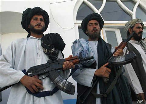 Former Taliban fighters stand in line as they surrender their weapons to Afghan authorities in Herat, west of Kabul, Afghanistan, 19 June, 2010.