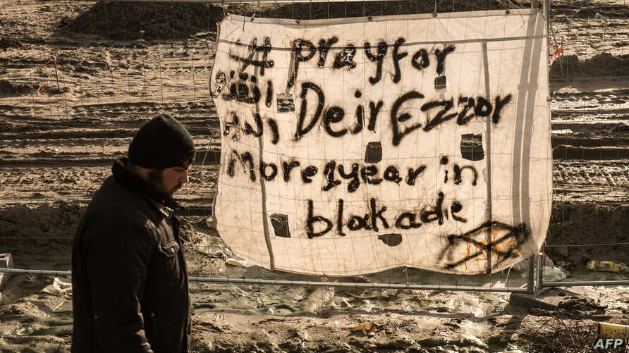 """FILE - A man walks past a banner reading """"Pray for Deir Ezzor"""" at the migrant camp known as the """"Jungle"""" in Calais, France, Dec. 7, 2015."""