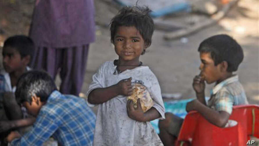 Indian street children eat food at a shanty town in Hyderabad, 13 Oct 2010