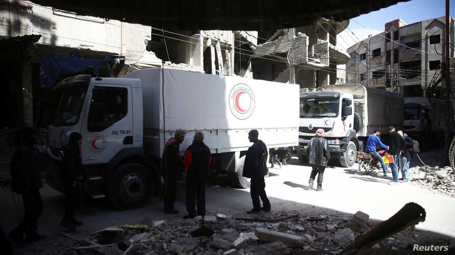 People are seen around Red Crescent aid truck in the besieged town of Douma, Eastern Ghouta, in Damascus, Syria, March 9, 2018.