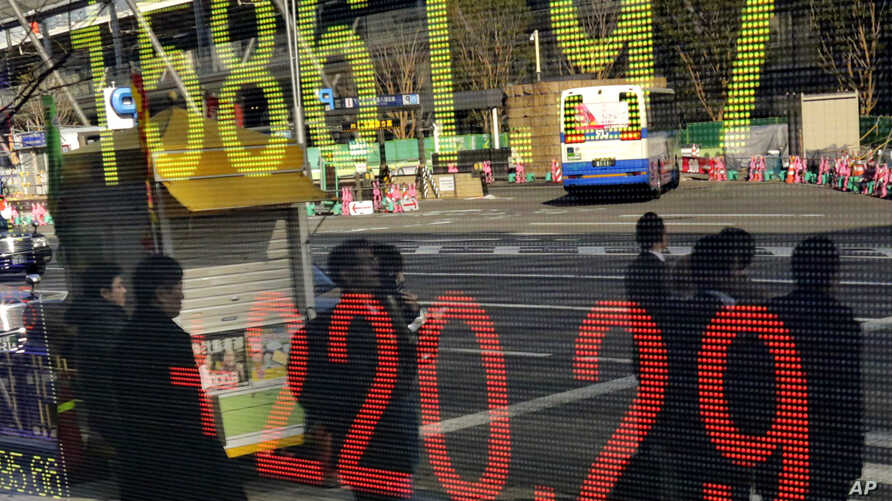 People wait to cross the street in front of an electronic stock indicator in Tokyo, Jan. 21, 2014.