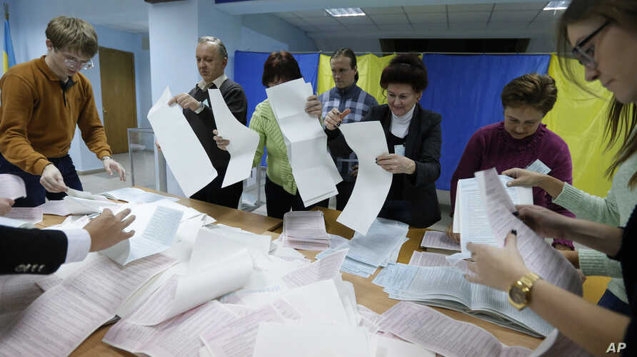 Members of a local election commission count ballots at a polling station in Kyiv, Ukraine, Oct. 25, 2015.