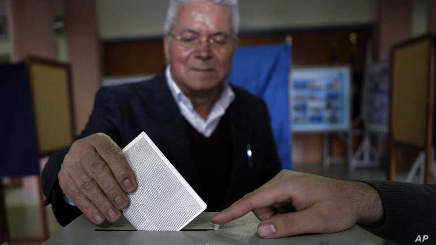 A man votes in the Presidential election in southern port city of Limassol, Cyprus, February 17, 2013.