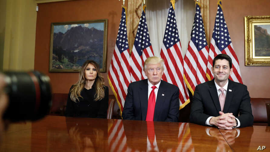 President-elect Donald Trump, his wife Melania and Vice president-elect Mike Pence, talk as they pose for photographers with House Speaker Paul Ryan.