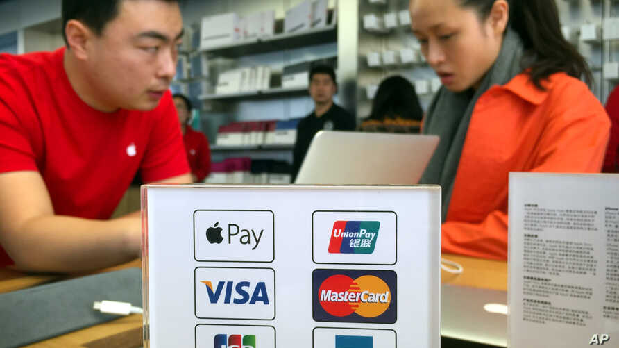 An employee works on a laptop computer as he talks with a customer near a sheet showing accepted methods of payment, including, beginning Thursday, Apple Pay, top left, at an Apple Store in Beijing, Feb. 18, 2016.