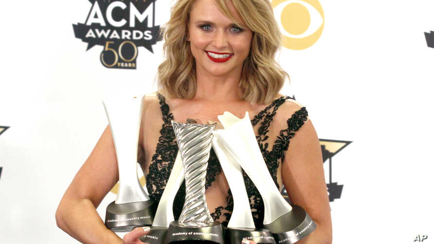 """Miranda Lambert poses in the press room with the milestone award and the awards for song of the year for """"Automatic"""", album of the year for """"Platinum"""" and female vocalist of the year at the 50th annual Academy of Country Music Awards at AT&T Stadium,..."""