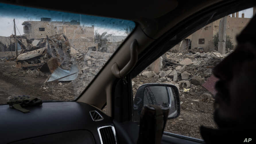 A U.S.-backed Syrian Democratic Forces (SDF) fighter rides past destroyed homes and vehicles in a village recently retaken from Islamic State militants in Susah, Syria, Feb. 16, 2019.