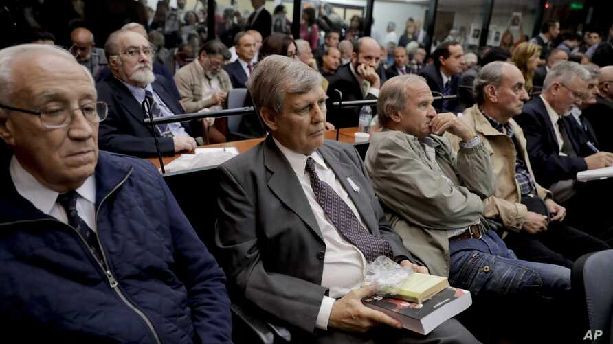 """Jorge Eduardo Acosta, left, a former navy captain; Alfredo Astiz, second left, a former navy spy nicknamed """"the Angel of Death;"""" and other former members of the Argentine armed forces sit in a courtroom in Buenos Aires, Argentina, Nov. 29, 2017. Acos"""