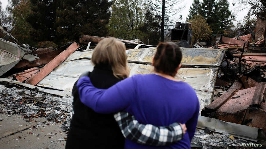 Irma Corona, right, comforts neighbor Gerryann Wulbern in front of the remains of Wulbern's home after the two returned for the first time since the Camp Fire in Paradise, Calif., Nov. 22, 2018.