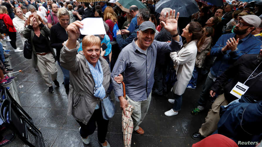 Voters are applauded as they leave a polling station for the banned independence referendum in Barcelona, Spain, Oct.  1, 2017.