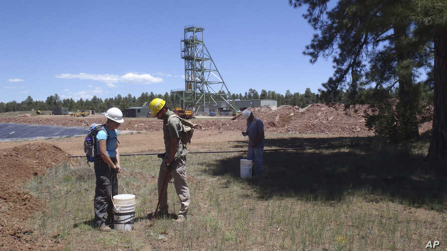 In this June 7, 2013, file photo provided by the U.S. Geological Survey, scientists, from left, Christine Dowling, Adam Benthem, and David Naftz collect soil samples on the Canyon Mine property in Arizona.
