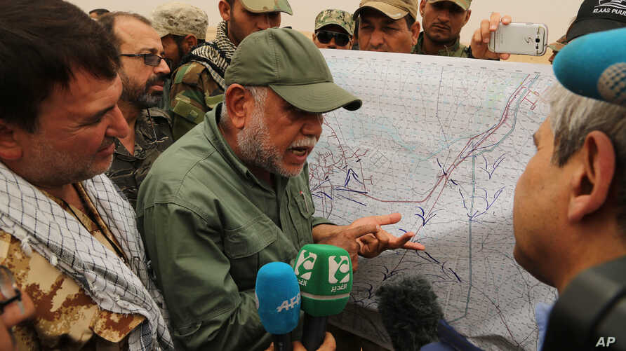 Iraqi militia leader Hadi al-Amiri of the Badr Brigades Shiite militia explains a battle plan to his fighters near the front line on the outskirts of Fallujah, Anbar province, Iraq, June 1, 2015.