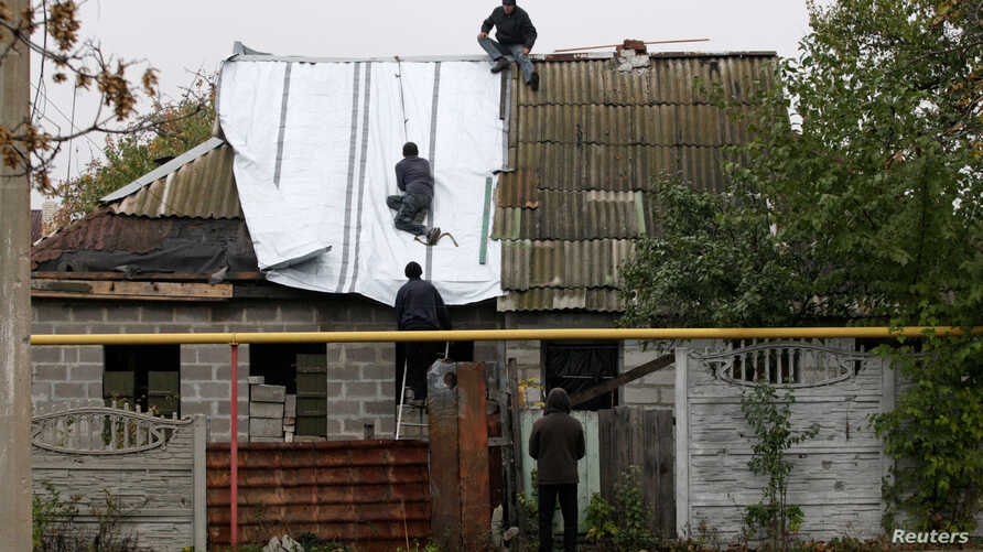 People fix the roof of a house, damaged in fighting between Ukrainian troops and rebels, in the Oktyabrsky district of Donetsk, Ukraine, Oct. 25, 2017.