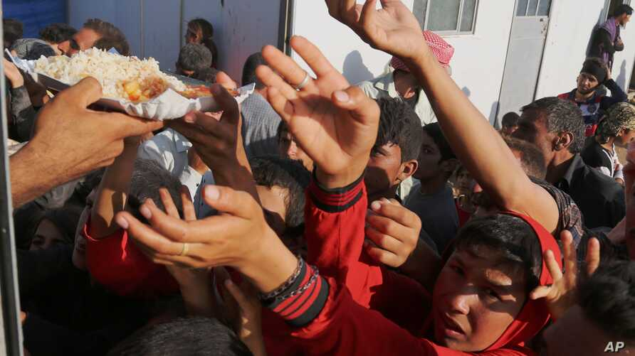 FILE - Displaced Iraqis from the Yazidi community gather for food at the Nowruz camp, in Derike, Syria, Aug. 12, 2014.