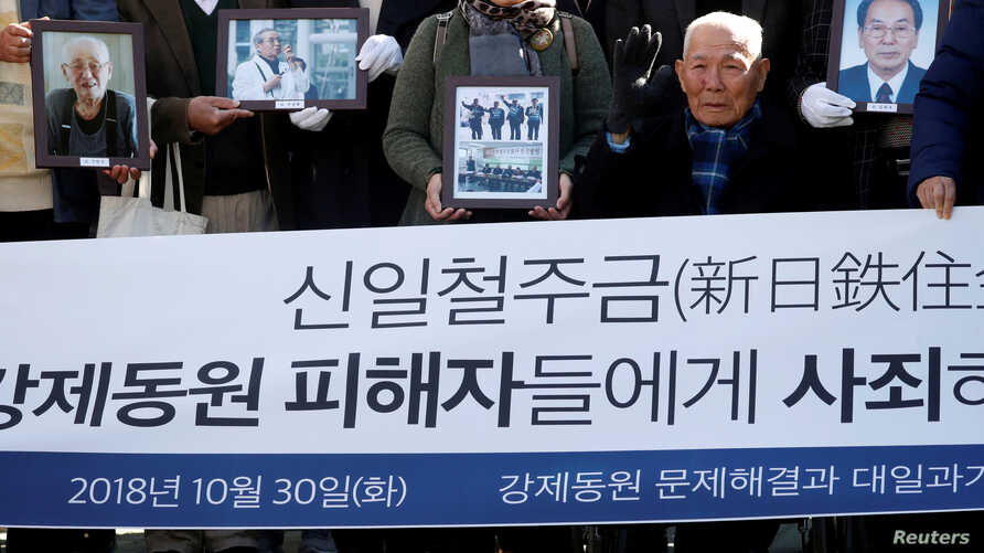 "FILE - Lee Choon-shik, a victim of wartime forced labor during the Japanese colonial period, arrives with supporters holding portraits of fellow deceased laborers in Seoul, Oct. 30, 2018. The banner reads ""Nippon Steel & Sumitomo Metal Corp apologize"