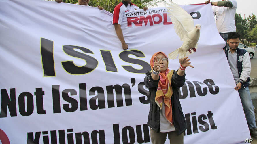 FILE - A Muslim woman releases a dove as a symbol of peace during a rally against the Islamic State group in Jakarta, Indonesia, Sept. 5, 2014.