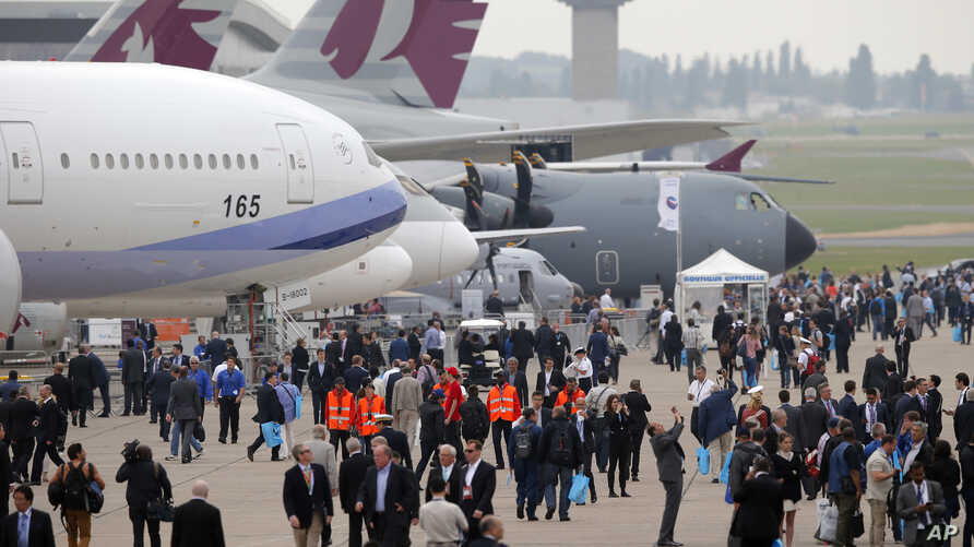 Visitors walk by a Boeing 777-300ER of China Airlines at left, and and Airbus A400M, at right, during the Paris Air Show, at Le Bourget airport, east of Paris, June 15, 2015.