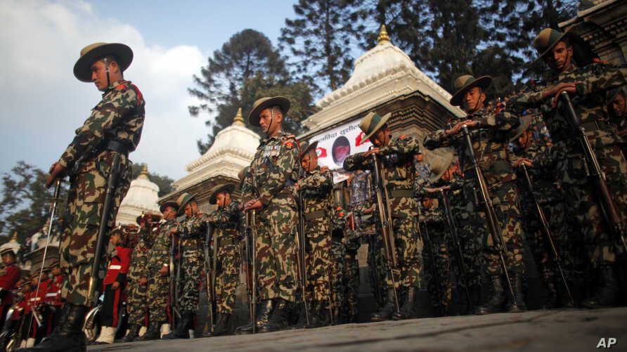 FILE - Nepalese army soldiers give a guard of honor during the cremation of Nepalese prime minister Sushil Koirala, on the banks of the Bagmati River in Kathmandu, Nepal.