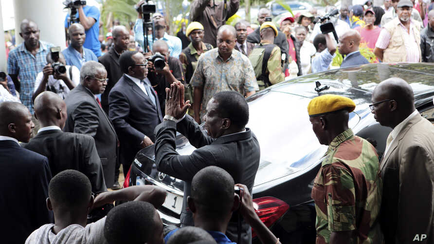 Zimbabwe President Emmerson Mnangagwa, center, leaves after paying his respects to the family of Morgan Tsvangirai, in Harare, Feb. 18, 2018.