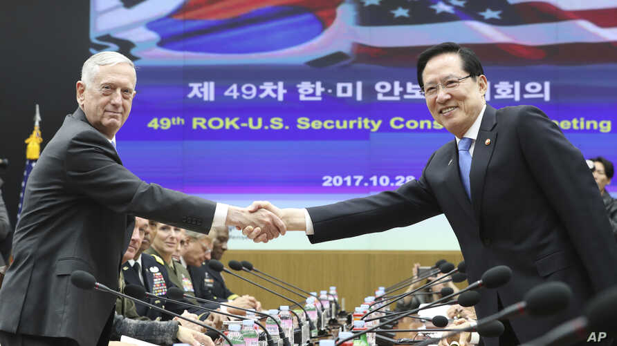 U.S. Defense Secretary Jim Mattis, left, and South Korean Defense Minister Song Young-moo shake hands while posing for a photo before the 49th Security Consultative Meeting at Defense Ministry in Seoul, South Korea, Oct. 28, 2017.