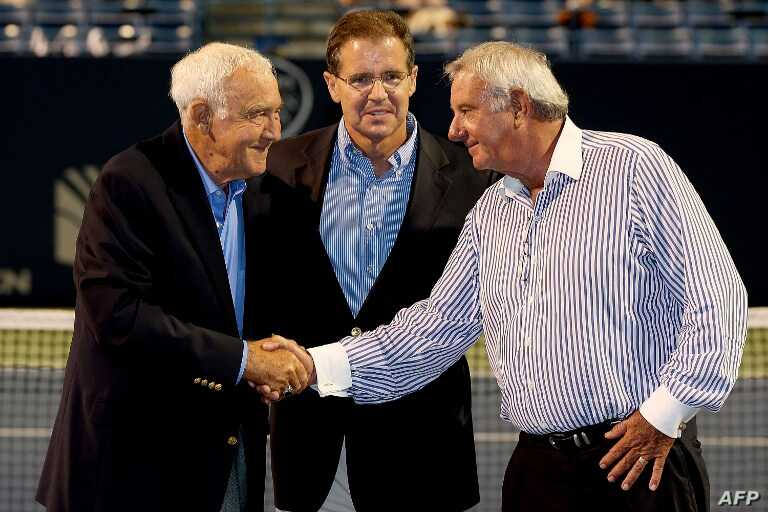 After being inducted into the International Tennis Hall of Fame, Mike Davies, left, thanks Butch Buchholz, right, chairman of the New Haven Open at Yale, and Mark Stenning, CEO of the hall, in New Haven, Conn., Aug. 24, 2014.