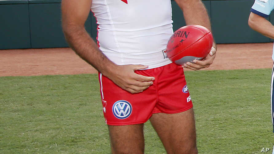 FILE - In this March 19, 2014 photo, Sydney Swans player Adam Goodes holds an Australian Rules Football at the Sydney Cricket Ground. Australians tend to laud their champions, so the fact that crowds continue to loudly boo him when he plays for the S
