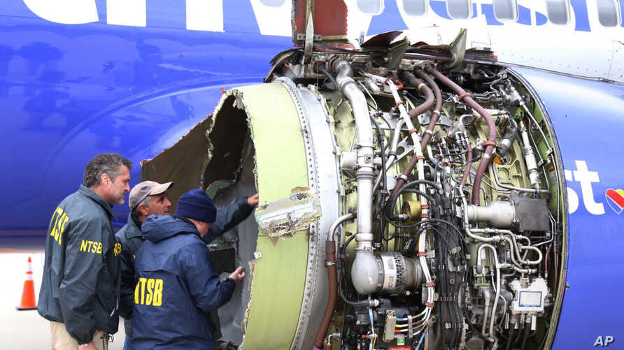 National Transportation Safety Board investigators examine damage to the engine of the Southwest Airlines plane that made an emergency landing at Philadelphia International Airport in Philadelphia, April 17, 2018.
